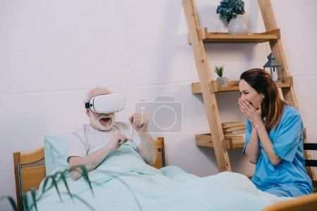 Photo for Nurse feeling excited about old man using vr glasses in bed - Royalty Free Image