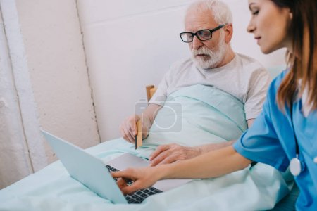 Nurse helping senior patient using laptop and credit card