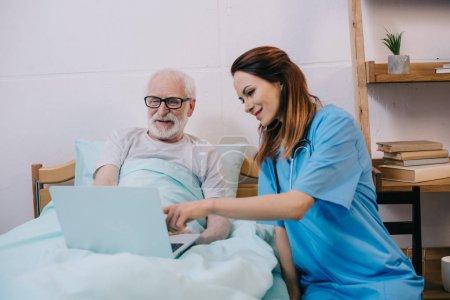 Nurse pointing at laptop in senior patient hands