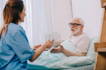 Nurse helping senior patient in bed to hold a cup