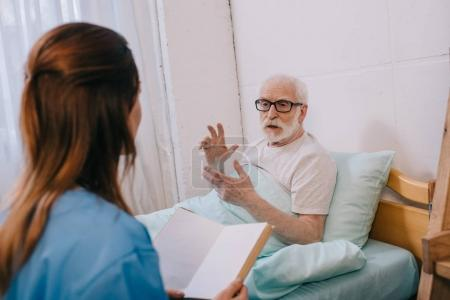 Old man patient and nurse discussing plot of the book