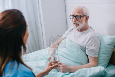 Photo for Nurse giving old man in bed a glass of water - Royalty Free Image