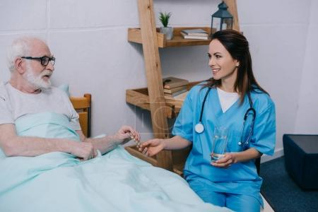 Senior patient in bed taking medications from female nurse