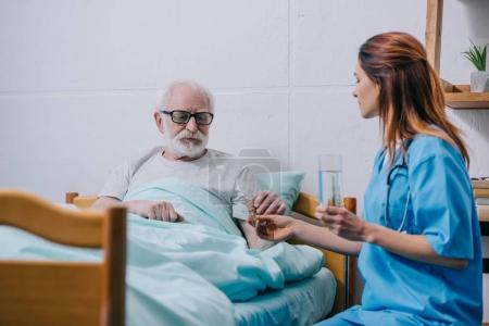 Nurse giving a glass of water to patient with pills