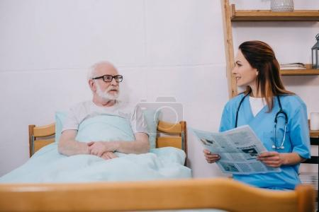 Nurse reading newspaper to senior patient