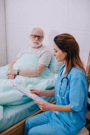 Nurse explaining medical advice to old patient in bed