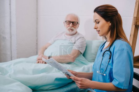 Nurse explaining diagnosis to old patient in bed