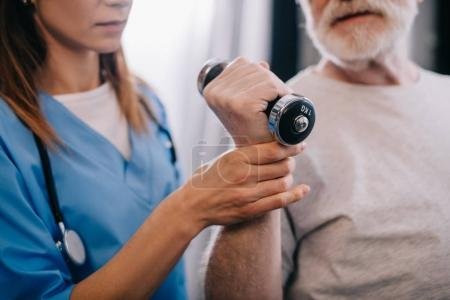 Photo for Old man with dumbbell and nurse during physiotherapy - Royalty Free Image