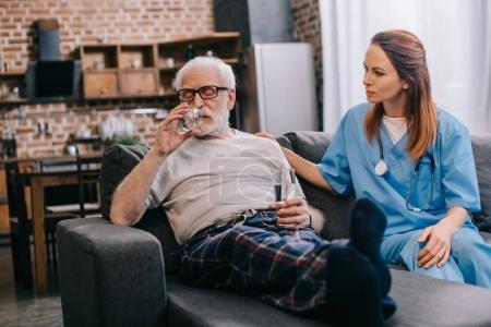 Senior man taking pills and nurse sitting on sofa