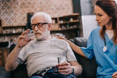 Nurse sitting by senior man taking medications