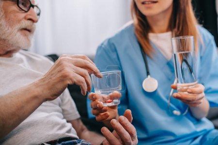 Female nurse giving pills to senior patient