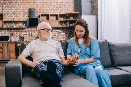 Female nurse checking heartbeat of senior man