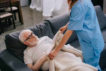Nurse helping old patient to cover with plaid