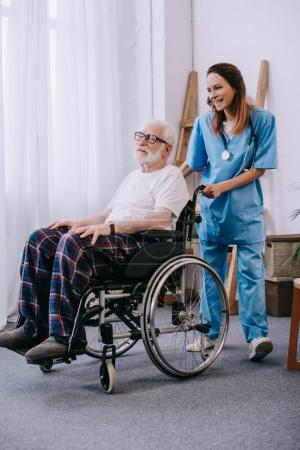 Nurse pushing wheelchair with senior patient