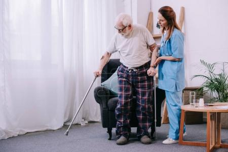 Nurse helping male patient with crutches