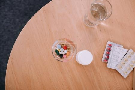Different colorful pills and capsules with glass of water on table