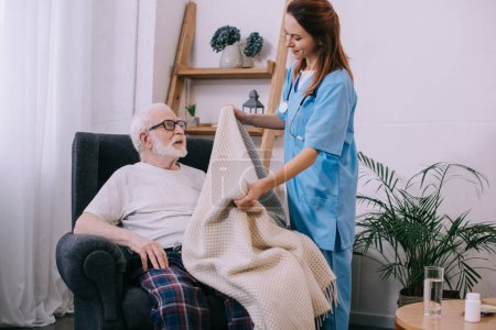 Photo pour Infirmier accompagnement patient senior avec plaid - image libre de droit