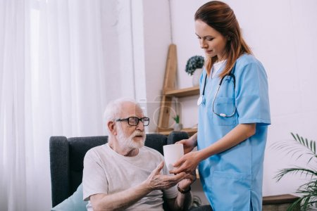 Nurse helping senior patient to hold a cup