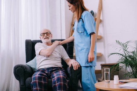 Nurse supporting and holding shoulder of smiling senior man patient