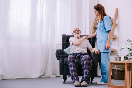 Female caregiver supporting senior man patient