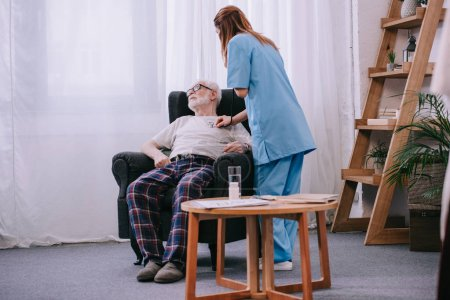 Nurse with stethoscope checking heart rate of senior patient