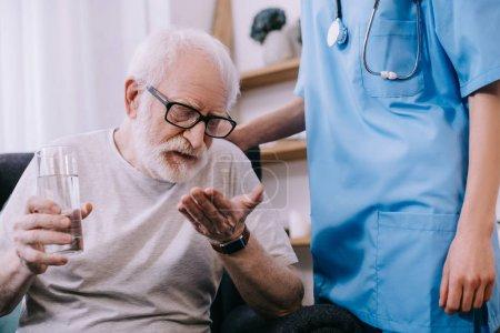 Caregiver standing by senior man taking medications