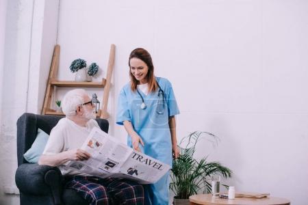 Nurse pointing at newspaper in senior patient hands