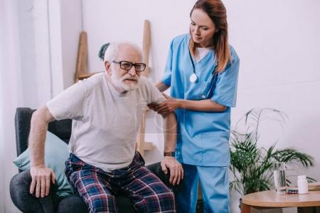Nurse helping old man to stand up from chair
