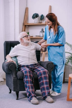 Caregiver holding hand of smiling senior man patient