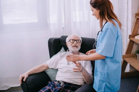 Nurse giving a glass of water to senior patient