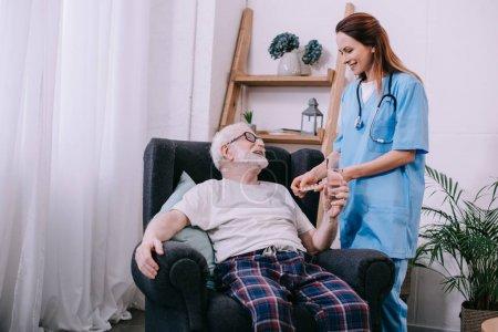 Senior patient taking medications from female nurse