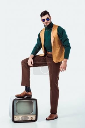 handsome retro styled man putting leg on vintage television on white
