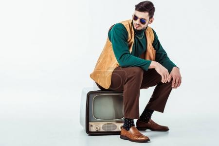 handsome retro styled man sitting on vintage television on white