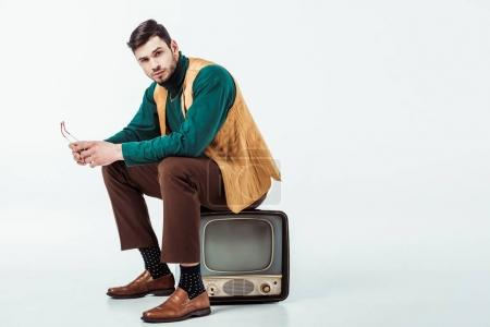 handsome retro styled man sitting on vintage television and looking at camera on white