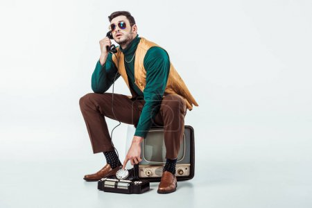 Photo for Handsome retro styled man sitting on vintage television and talking by stationary telephone - Royalty Free Image