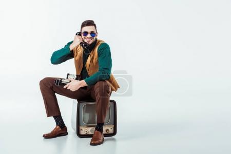 Photo pour Homme assis à la télévision vintage et de parler par téléphone fixe de style rétro souriant - image libre de droit