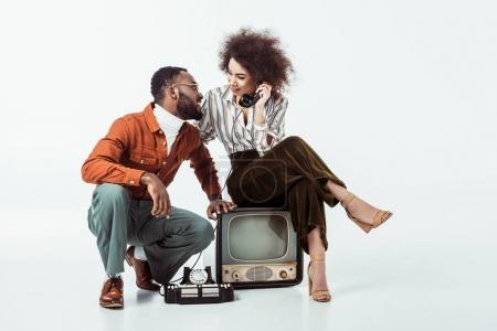 Photo for African american retro styled girlfriend sitting on vintage television and and talking by phone on white - Royalty Free Image