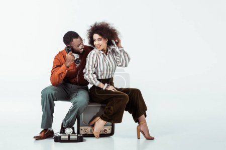 happy african american retro styled couple sitting on vintage television with phone on white