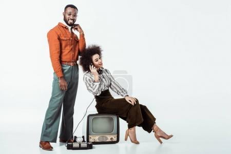 Photo for Happy african american retro styled girlfriend sitting on vintage television and and talking by phone on white - Royalty Free Image
