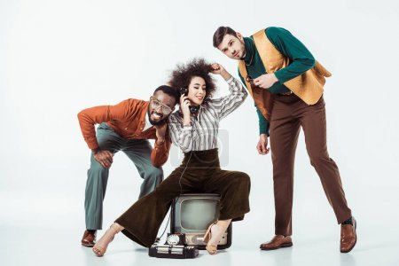 happy multicultural retro styled friends with vintage television and telephone on white