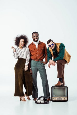 smiling multicultural retro styled friends with vintage television looking at camera on white