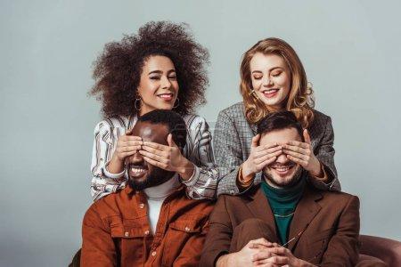 Foto de Feliz multicultural retro estilo a chicas cubriendo ojos multiétnico hombres aislados en gris - Imagen libre de derechos