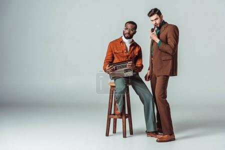 multicultural retro styled friends with radio and pipe on grey