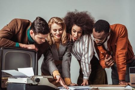 multiethnic retro styled journalists reading newspapers isolated on grey