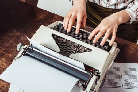 cropped image of retro styled african american writer typing on typewriter