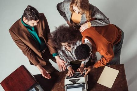 Photo pour Overhead view of multicultural retro styled journalists looking at typewriter - image libre de droit