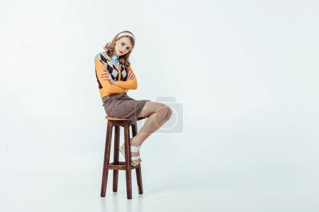Photo for Retro styled girl sitting on wooden chair with crossed arms and looking at camera on white - Royalty Free Image