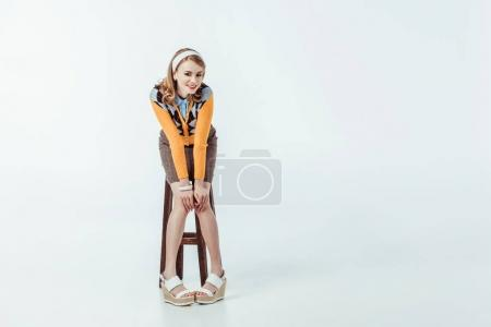 Photo for Happy beautiful retro styled girl sitting on wooden chair and looking at camera on white - Royalty Free Image