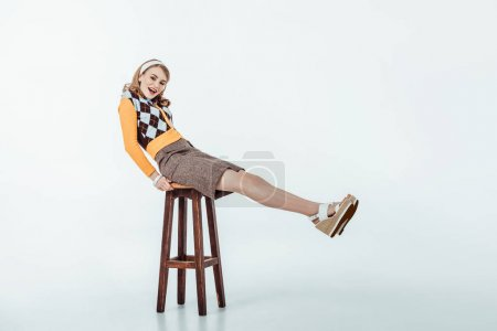 Photo for Smiling beautiful retro styled girl sitting on wooden chair and looking at camera on white - Royalty Free Image