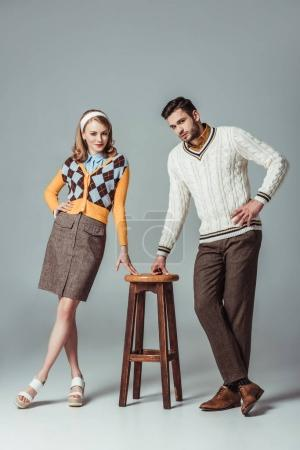 beautiful retro styled couple posing with wooden chair on grey